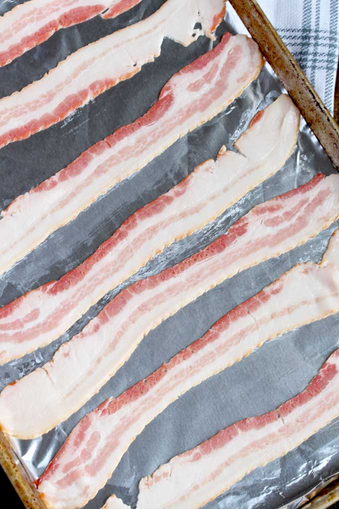 Raw bacon slices layered on a rimmed baking sheet.