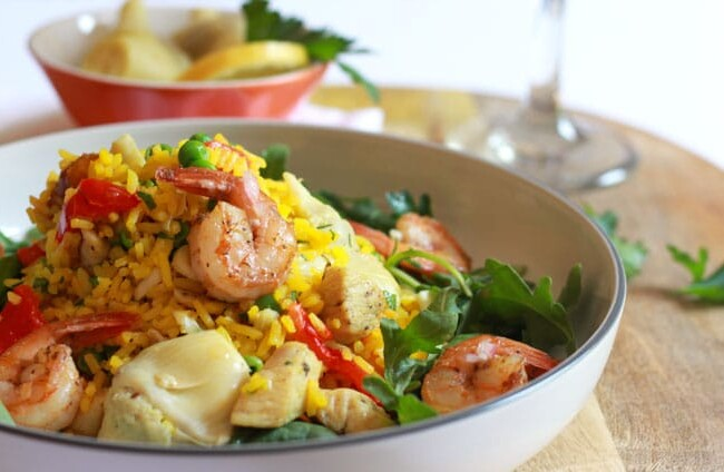 Easy and Fool Proof Paella Salad. Perfectly cooked saffron infused rice with chicken and shrimp, artichoke hearts, roasted red peppers and peas on a bed of arugula and spinach lightly tossed in a delicious garlic vinaigrette