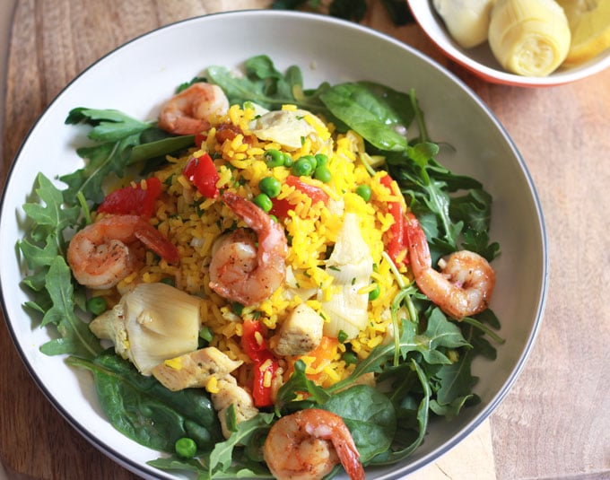 Easy and Fool Proof Paella Salad. Perfectly cooked saffron infused rice with chicken and shrimp, artichoke hearts, roasted red peppers and peas on a bed of arugula and spinach lightly tossed in a delicious garlic inaigrette