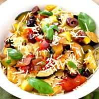 Pasta and veggies topped with Parmesan in a white bowl