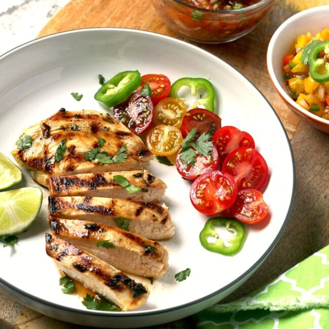 Sliced grilled chicken on a white plate.