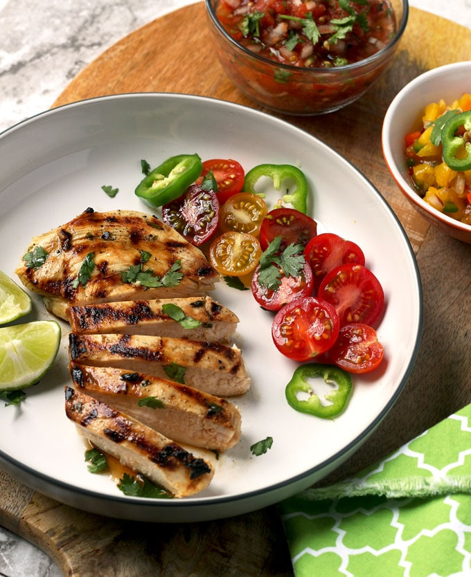 Boneless and skinless Tequila Lime Chicken breast sliced on a white plate surrounded by a tomato salad and lime wedges.