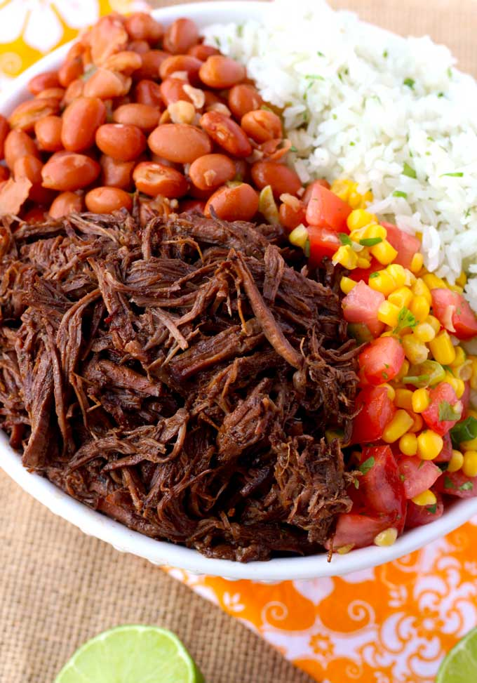 In this photo shredded barbacoa beef in a white bowl served with rice, beans and corn salsa
