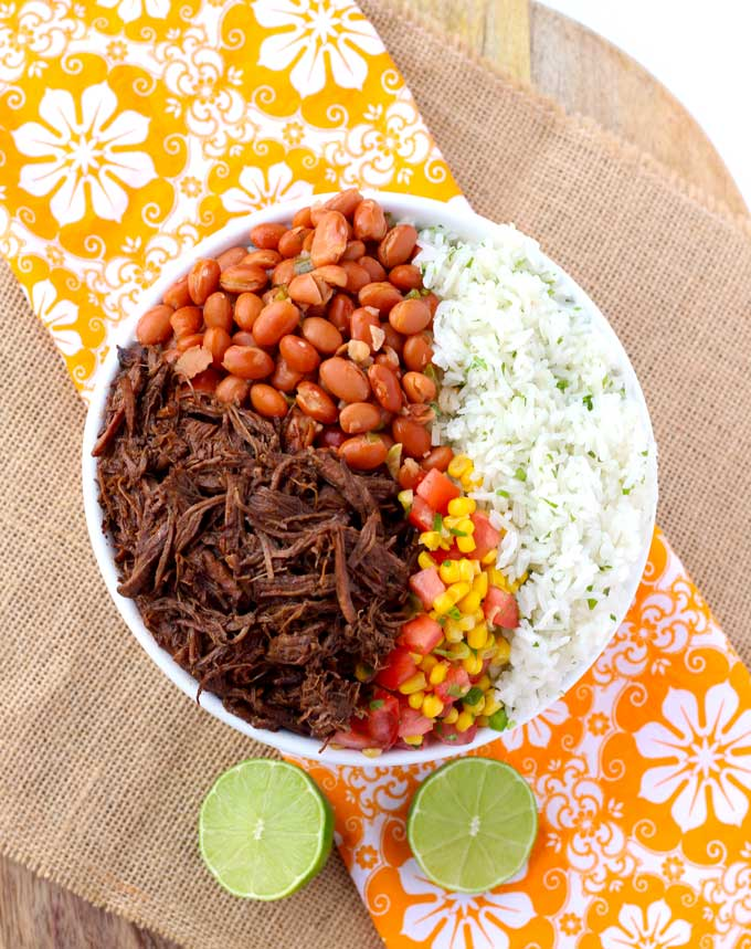 Top view of a barbacoa beef bowl with cilantro rice and pinto beans