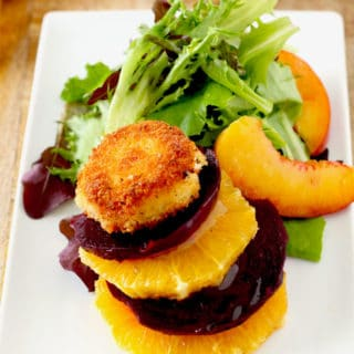 View of a stack of sliced beets and oranges topped with a crispy goat cheese coin next to salad greens and sliced peaches.