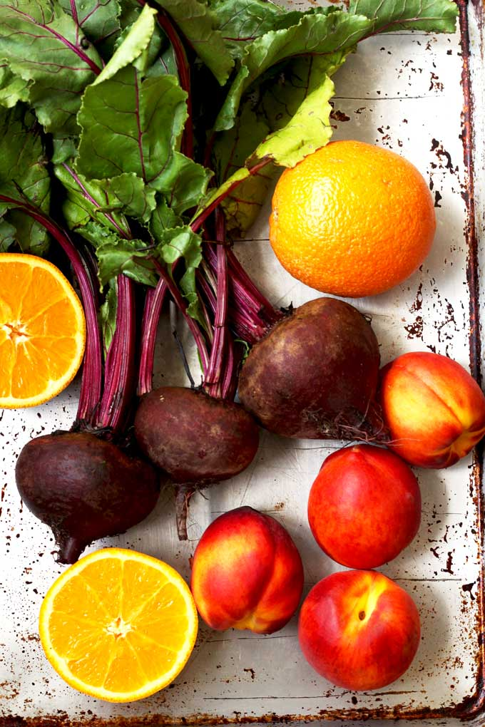 Ingredients for the roasted beet salad on a sheet pan. Whole beets with their green tops, oranges and peaches.