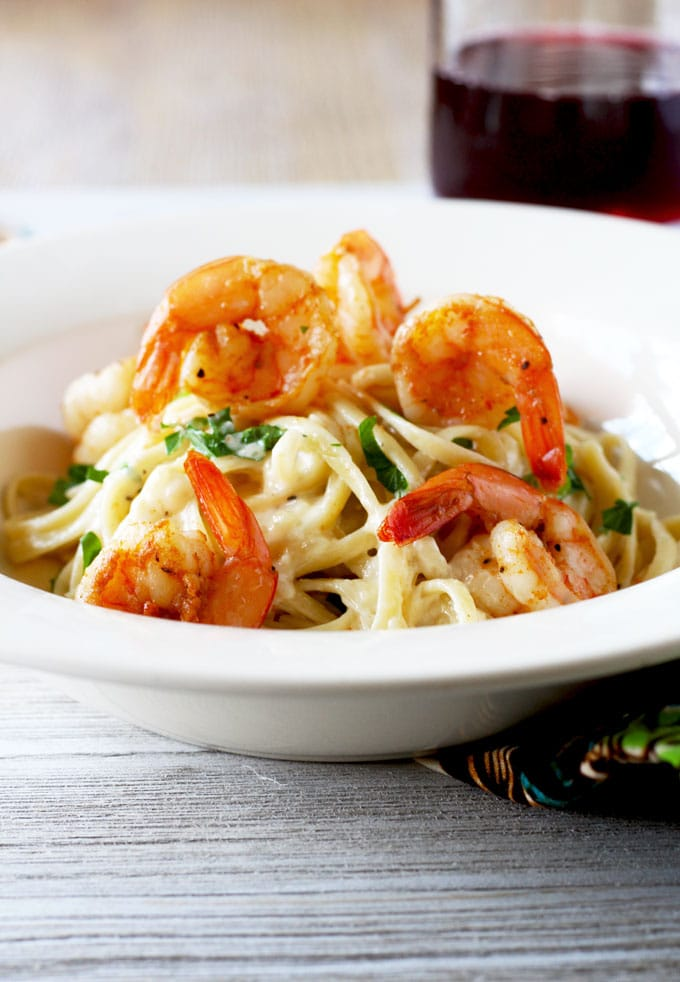 Picture here is a big mount of Shrimp Alfredo Pasta on a white pasta bowl topped with Cajun shrimp.
