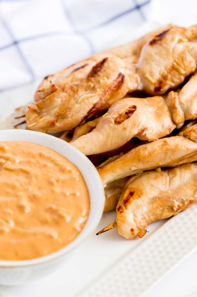 Chicken skewers on a plate next to a bowl of Thai dipping sauce.