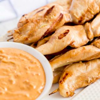 Grilled Chicken Skewers next to a bowl of dipping sauce