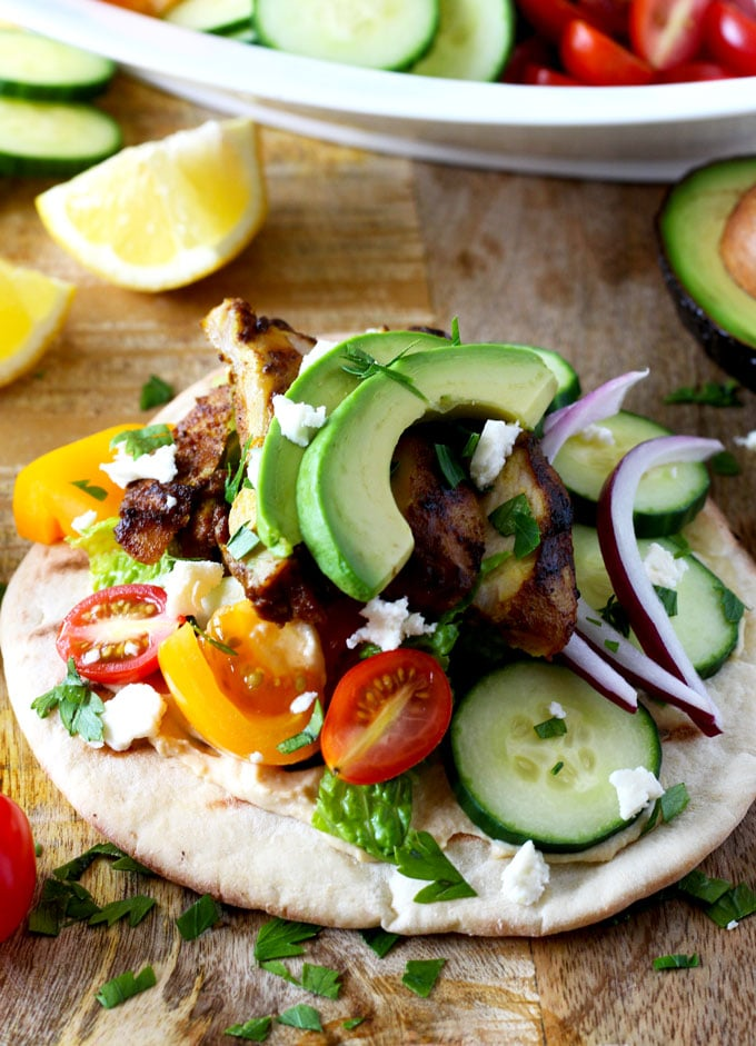 Chicken shawarma wrap with tomatoes and avocado on a wooden surface