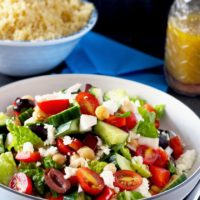 This Greek Chopped Salad is quick, easy, healthy and super tasty. Tomatoes, cucumbers, red onions, garbanzo beans, Kalamata olives and Feta cheese are tossed in a simple red wine-oregano vinaigrette.