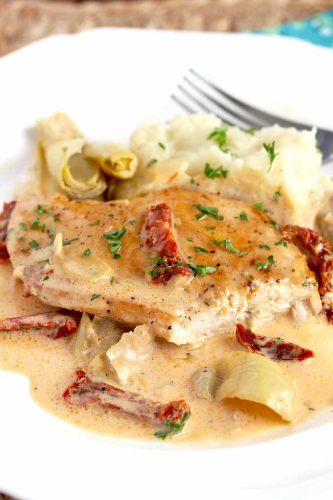 A piece of creamy chicken with artichoke hearts and sundried tomatoes on a white plate.