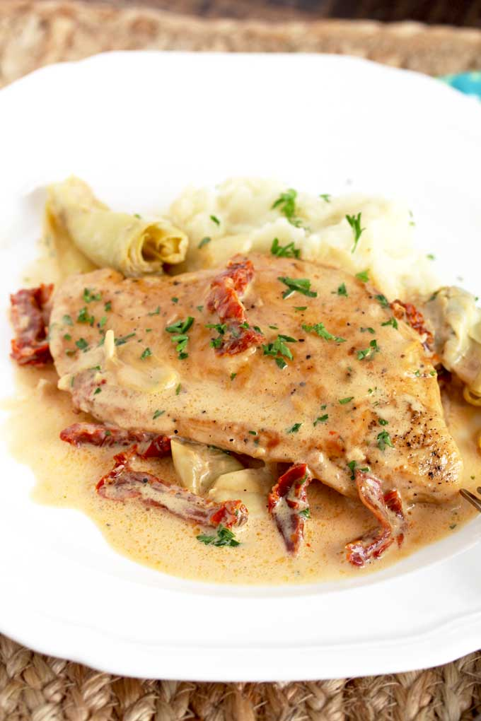 Creamy Chicken Breast served with mashed potatoes on a white plate.