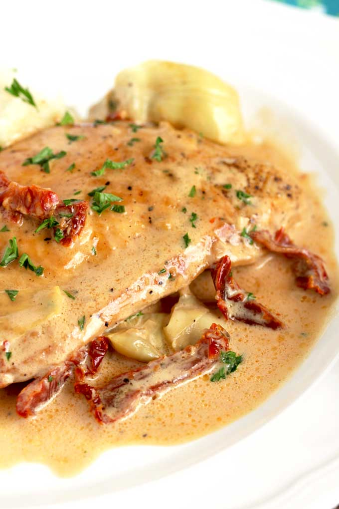 Close up view of creamy chicken with artichokes and sun dried tomatoes.