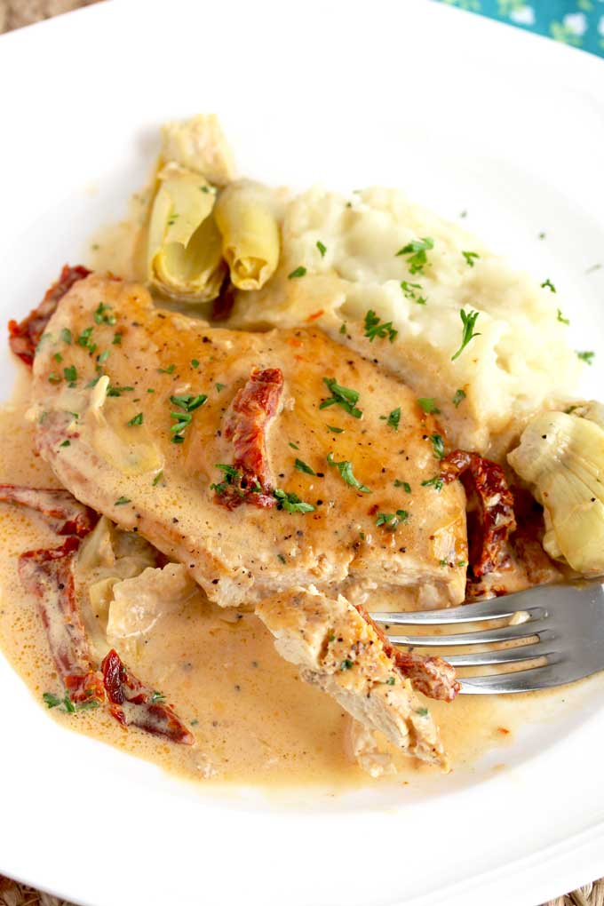 A piece of creamy chicken with artichokes and sun dried tomatoes
