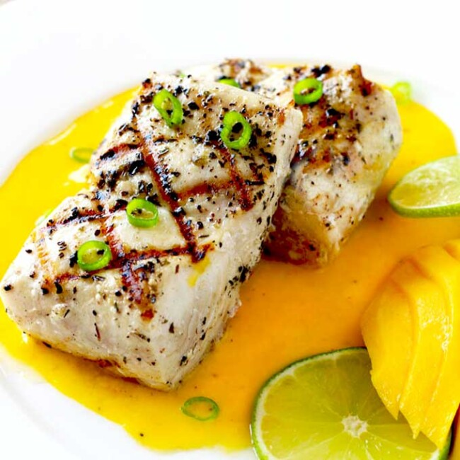 Grilled Mahi fish on a white plate served with mango sauce