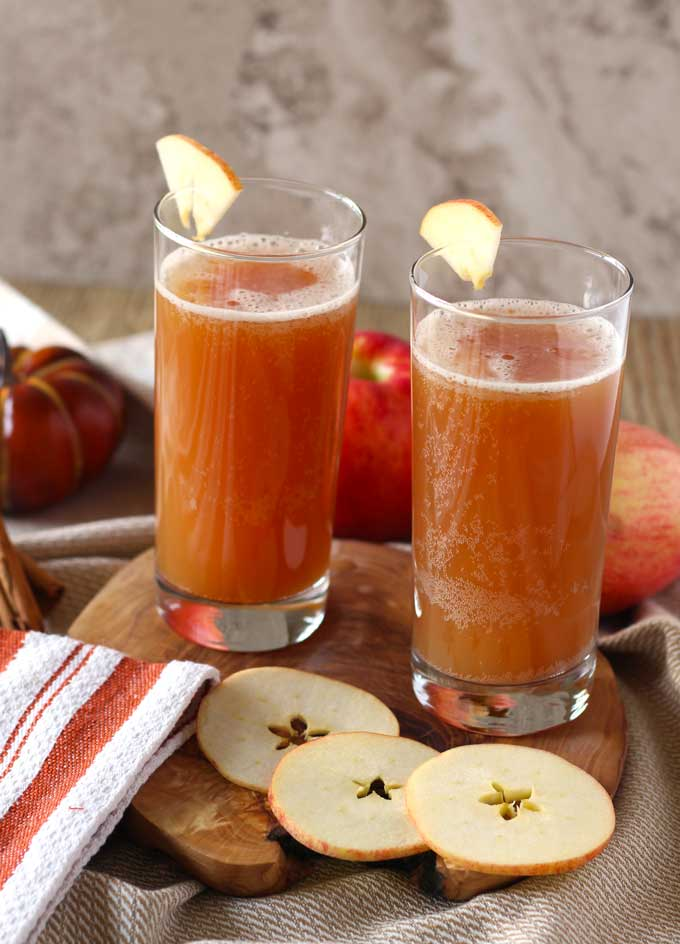 Two glasses of shandy garnished with apple slices