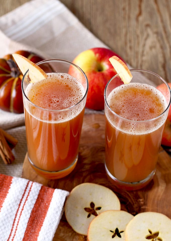 Two tall glasses with harvest shandy garnished with apple slices
