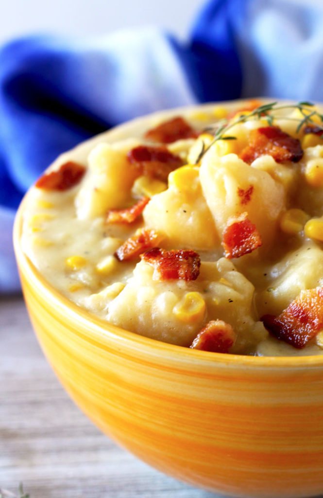 Close up view of the potato corn chowder on an orange ceramic bowl topped with crispy bacon pieces