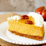 A sliced of creamy pumpkin spiced cheese cake topped with whipped cream and pecans on a white plate.