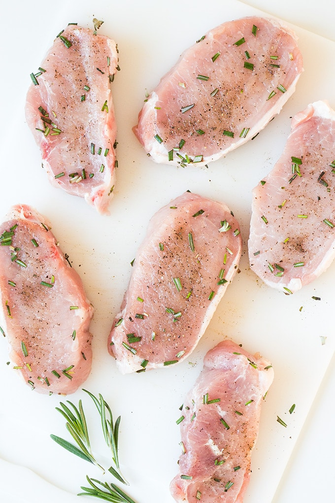 Raw pork chops seasoned with chopped rosemary