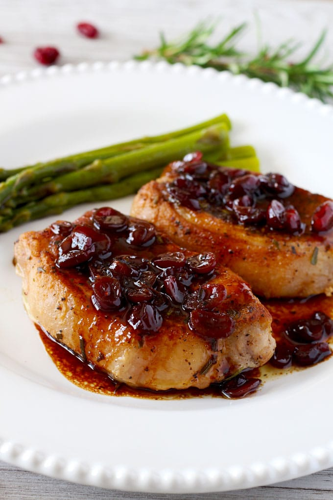 Two boneless pork chops with port and cranberries served on a white plate.