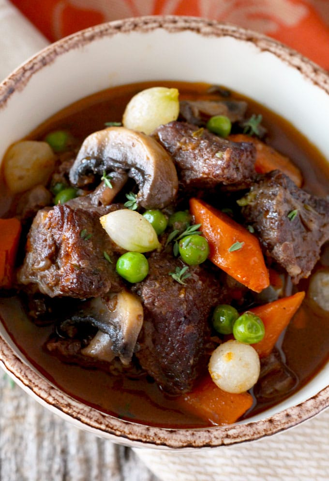 Close up view of stew in red wine with vegetables in a bowl
