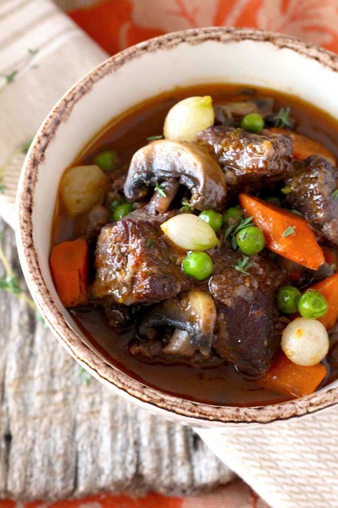 Tender pieces of beef, carrots, mushrooms onions and peas stewed in red wine in a bowl