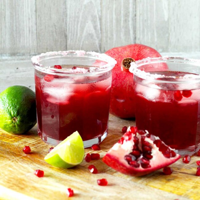 Two glasses of pomegranate margarita with salt on the rim
