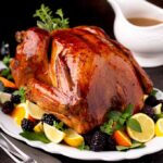 Golden brown whole roast turkey on a platter garnished with fresh herbs , citrus and fruit, next to a gravy boat.