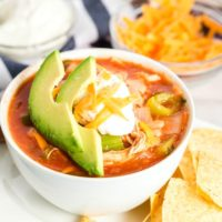 Tortilla soup with chicken in a white bowl.