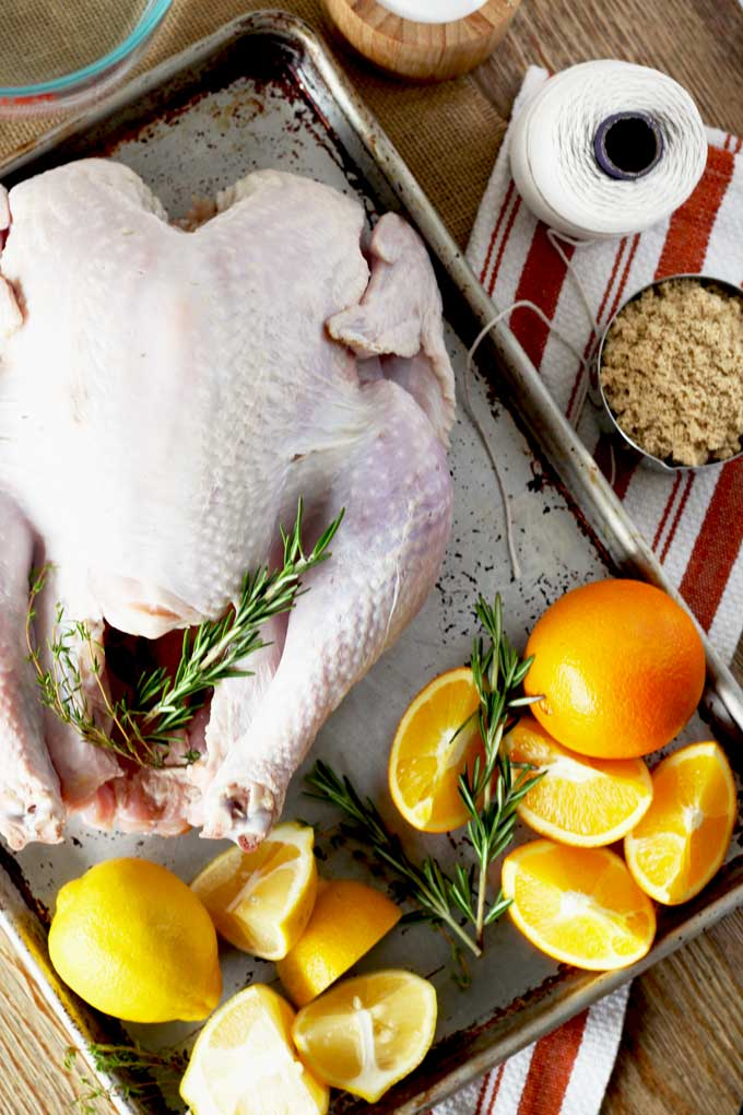 A sheet pan holds a raw whole turkey. There are also oranges, lemons and fresh rosemary surrounding the turkey. The sheet pan is sitting on a wooden table. There are also a measuring cup filled with brown sugar, a container of salt, a measuring pitcher with water and a roll of kitchen twine.