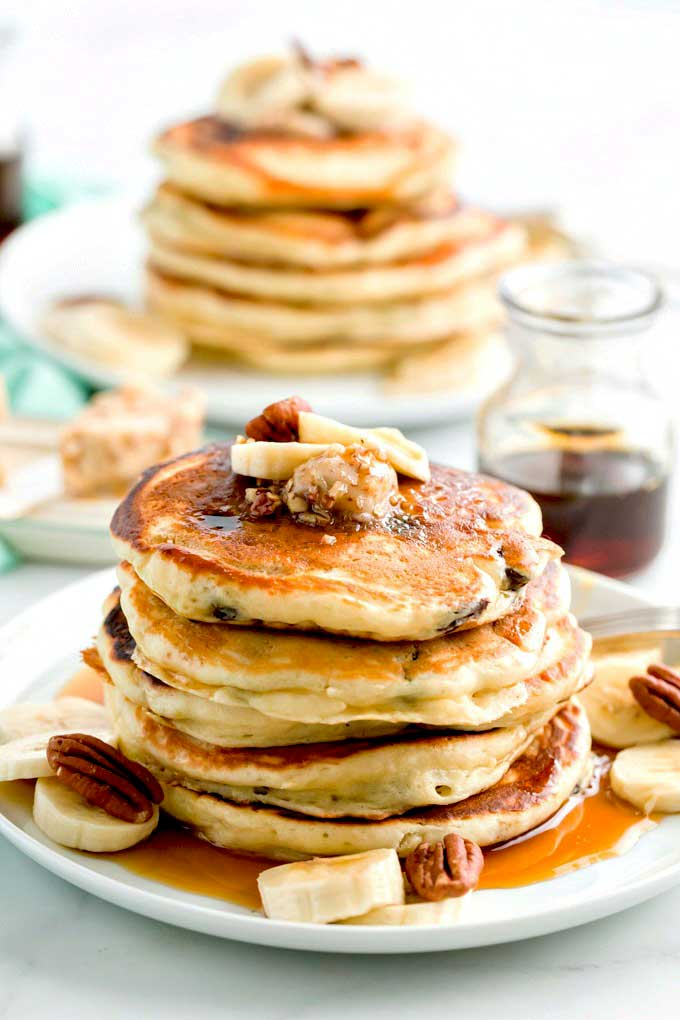 A stack of chocolate chip and banana pancakes topped with maple pecan butter