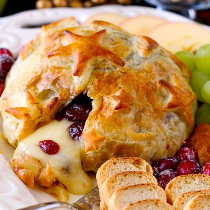Melted Baked Brie with Cranberries served with fruits and crackers on a white plate.