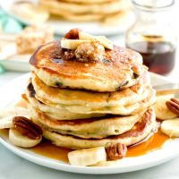 Chocolate Chip Banana Pancake stack with maple pecan butter on a white plate.