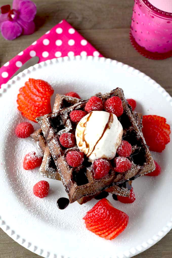 Overhead wiew of chocolate waffles on a white plate.