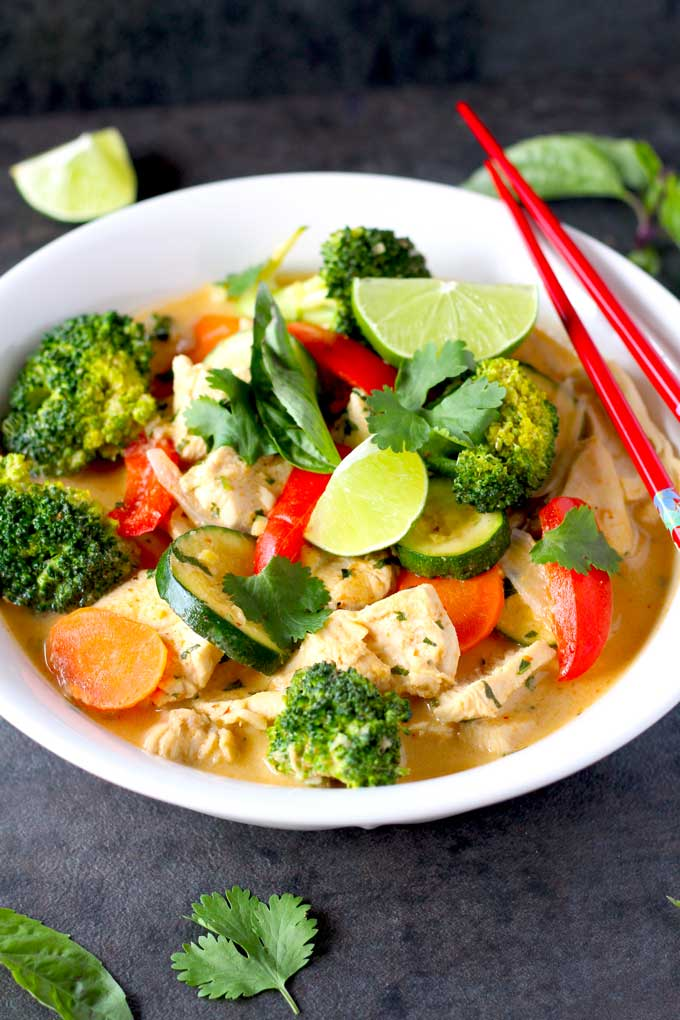 A big bowl of Thai Red Curry Chicken with Vegetables garnished with fresh herbs.