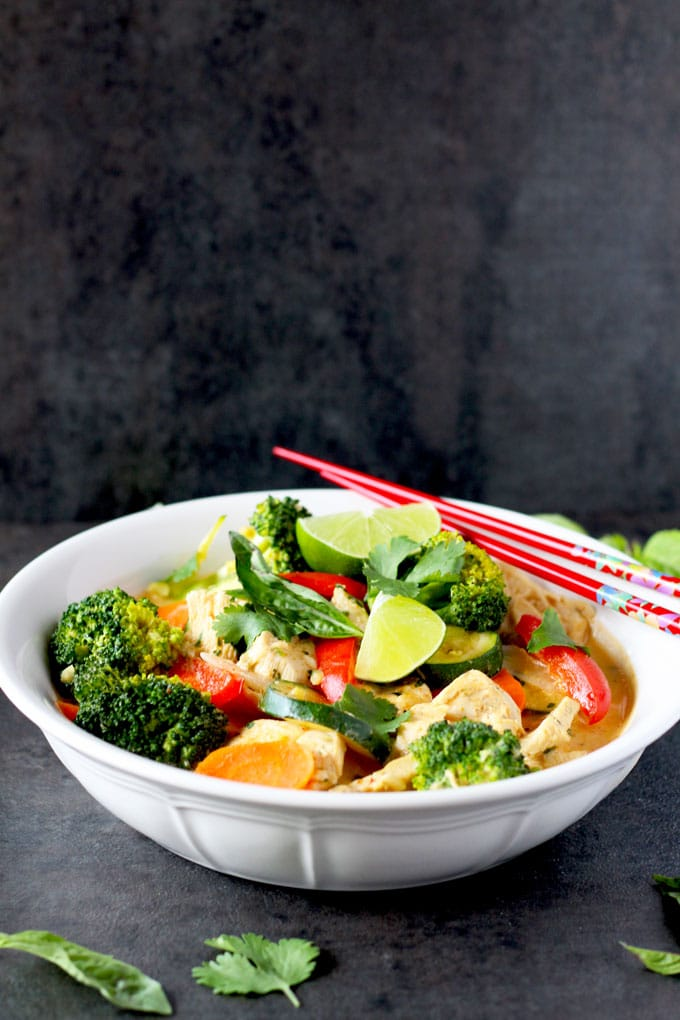 A white bowl of Thai Red Curry Chicken with Vegetables on a dark surface
