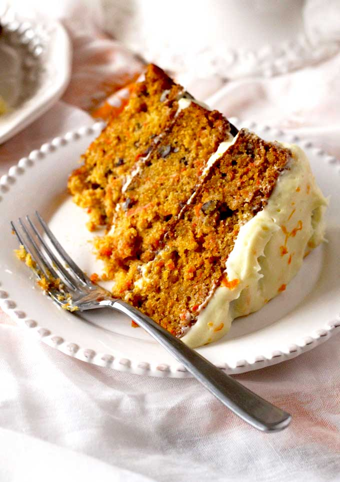 Slice of carrot cake with a piece missing on a white plate