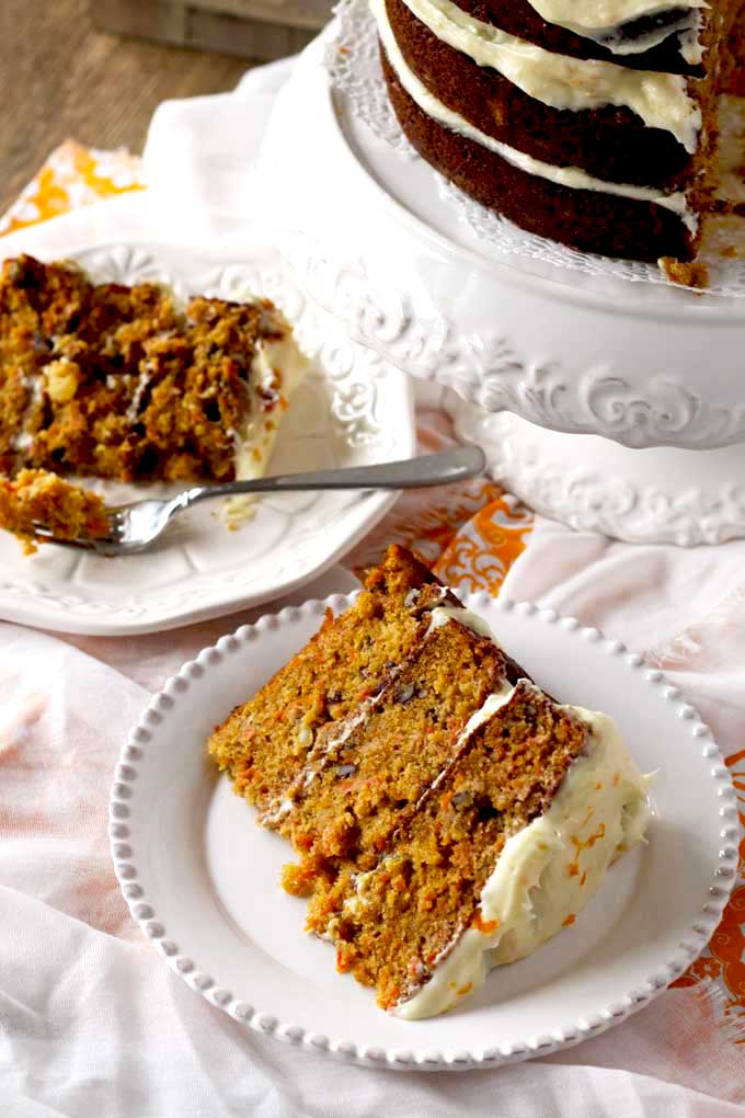 A sliced of carrot cake next to a whole cake.