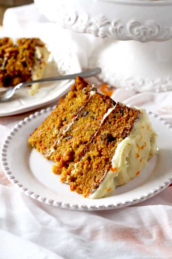 Carrot cake slice on a white plate.