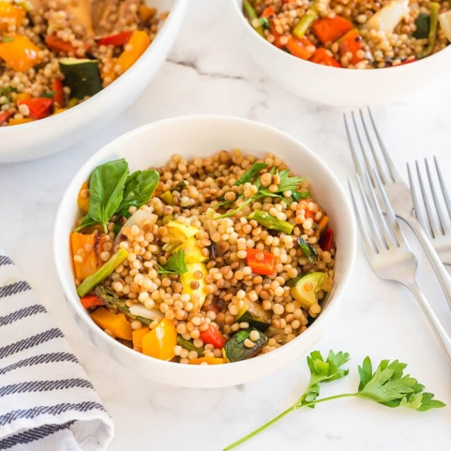 Pearled couscous salad and grilled veggies in a white bowl