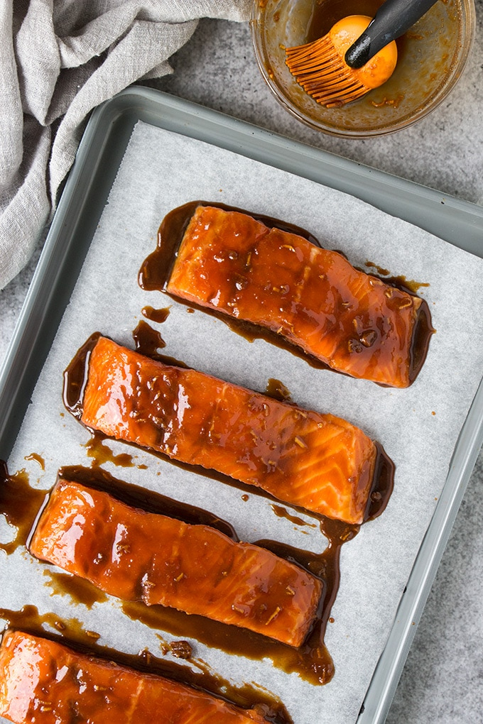 Salmon fillets on a sheet pan covered in miso glaze