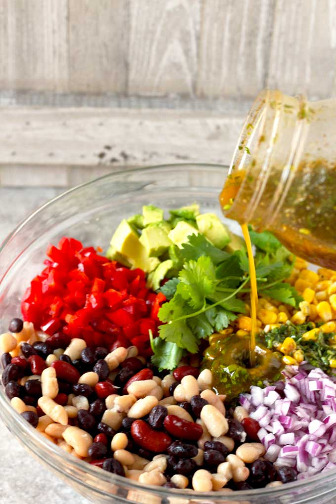 Citrus vinaigrette is been poured over the ingredients of the Mexican Three Bean Salad