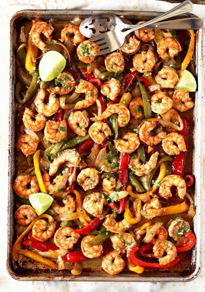 Spiced rubbed and marinated shrimp is oven roasted to perfection with onions and bell peppers and then smothered in a delicious cilantro lime butter. This Sheet Pan Shrimp Fajitas with Cilantro Lime Butter is quick, easy and incredibly flavorful!