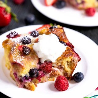 Tender and rich bread pudding topped with whip cream and garnished with fresh berries.
