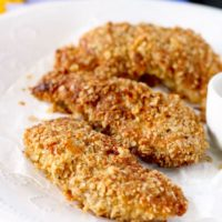This Crunchy Macadamia Nut Crusted Chicken Tenders are coated in a delicious savory crust made from oats, macadamia nuts, Parmesan cheese and spices! So delicious it will become a family favorite!