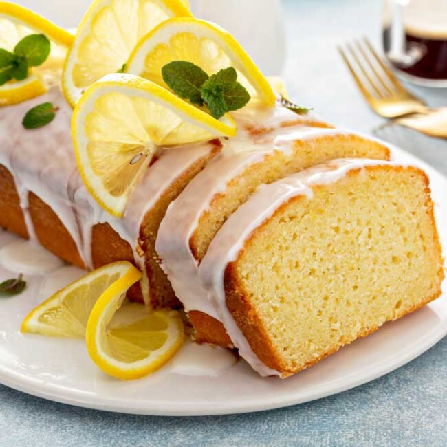 Lemon loaf drizzled with lemon glaze on a white plate