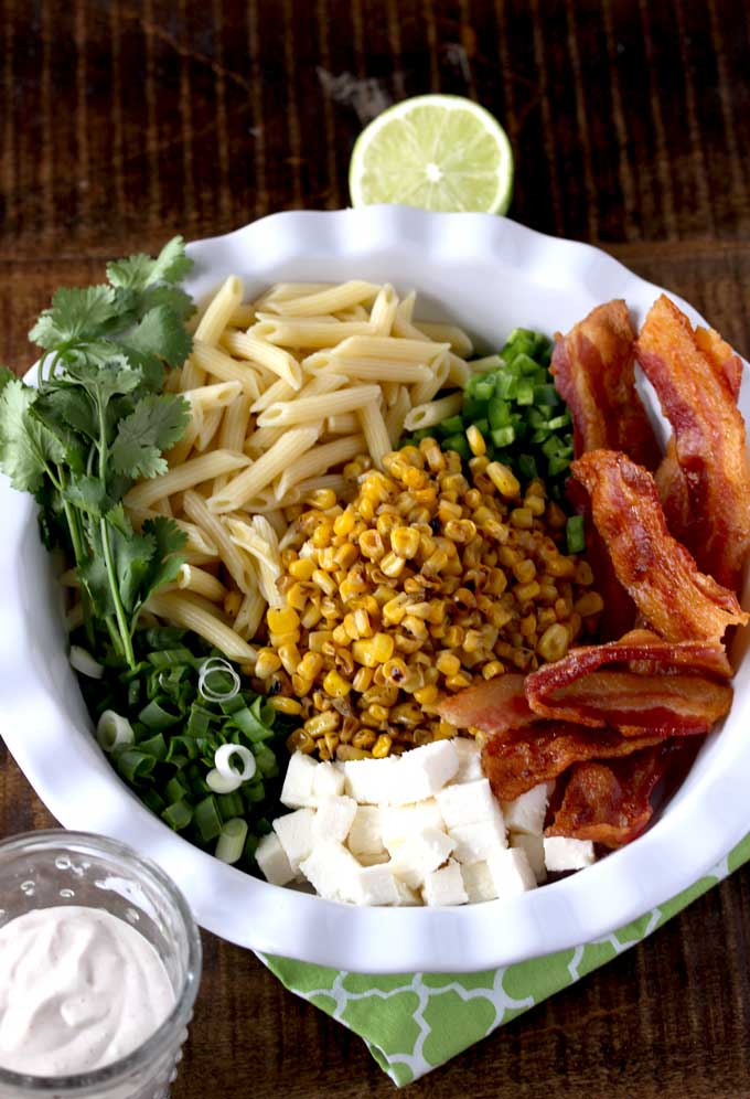 In a platter, ingredients to make Mexican Street Corn Pasta Salad. Roasted Corn, crispy bacon, cooked pasta, Cotija cheese, cilantro, jalapeno, green onions. In a small bowl you can see the dressing.