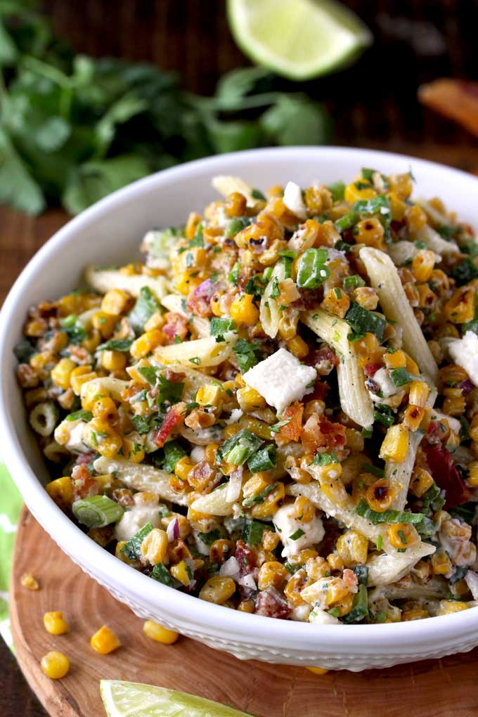 Pictured here a big bowl loaded with Mexican Street Corn Pasta Salad